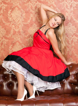 red sofa: beautiful young woman in a red dress on sofa