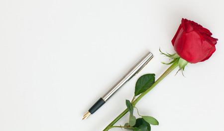 fountain pen and a red rose lying on a white sheet of paper photo