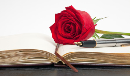 red rose on an open notebook lying on a wooden table Stock Photo
