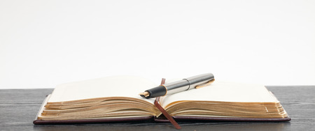 Opened notebook and a pen lying on a wooden table Stock Photo - 35847908