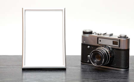 recollections: Vintage camera and photo frame on a wooden table on a white background