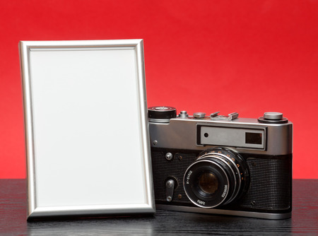 recollections: Vintage camera and photo frame on a wooden table on a red background