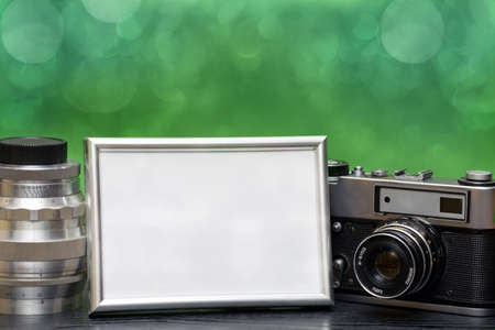 recollections: Vintage camera and photo frame on a wooden table on a beautiful background with bokeh