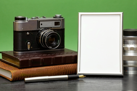 recollections: Vintage camera and photo frame on a wooden table on a green background