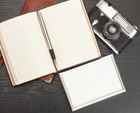 recollections: Photo, vintage camera and a notebook on a wooden table