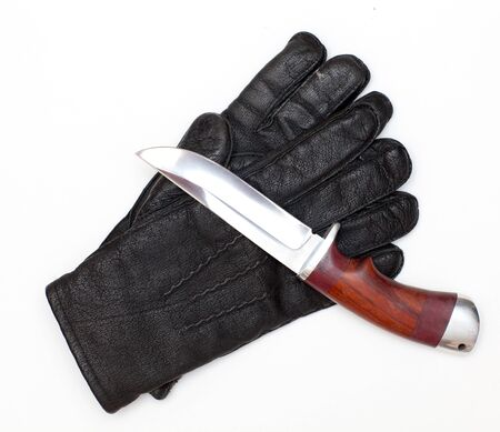 organized crime: Black leather gloves and a hunting knife on a white background Stock Photo