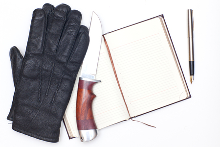 Black leather gloves, notebook and a hunting knife on a white background photo