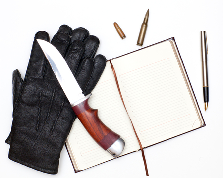 organized crime: Black leather gloves, notebook and a hunting knife on a white background Stock Photo