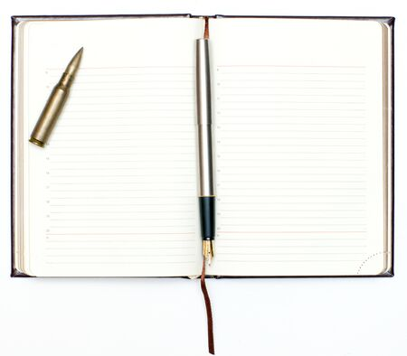 organized crime: Open notebook and a bullet lying on a white background