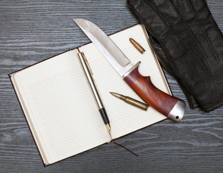 organized crime: Open notebook and a hunting knife lie on a wooden table