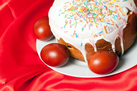 sateen: Easter cake and painted eggs on red cloth closeup Stock Photo