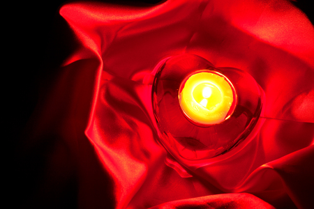 sateen: candle in the shape of hearts on a red background