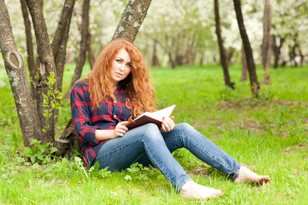 red jeans: beautiful red-haired woman writing in a notebook sitting on the grass near the tree