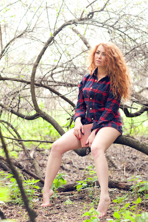Beautiful young red-haired woman in a shirt in the forest photo