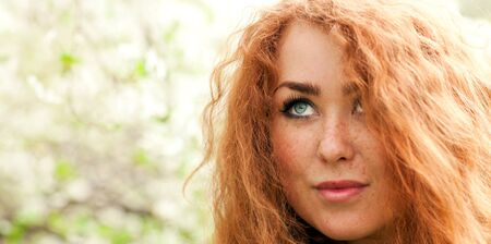 Beautiful face of young red-haired woman with freckles close-up photo