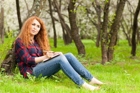 beautiful red-haired woman writing in a notebook sitting on the grass near the tree photo