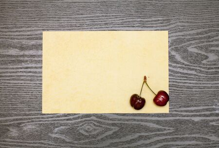 writ: Cherry on the old yellow piece of paper on a wooden table