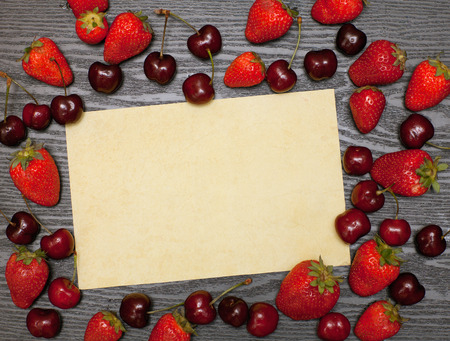 writ: Old yellow paper and berries on a wooden table Stock Photo
