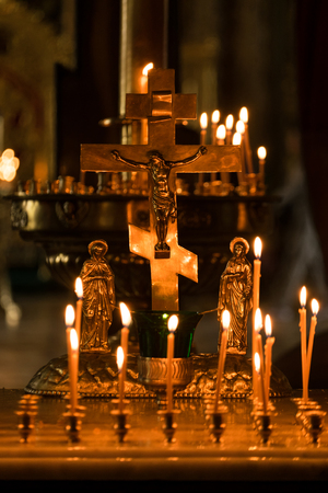 votive candle: Burning candles and Cross in a church Stock Photo
