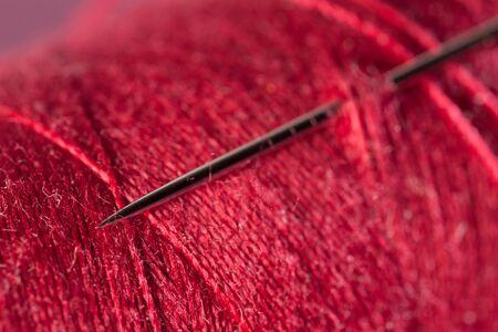 hilo rojo: Aguja de coser e hilo rojo primer plano
