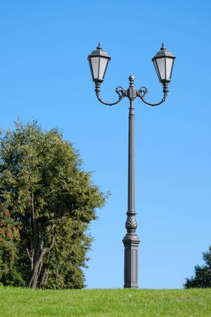 Lamppost on the green grass against the blue sky