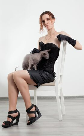 sits: Sphynx cat sits on a womans knees on gray background