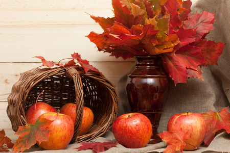 apples basket: Apples, basket and maple leaves on the table