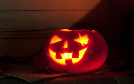 no teeth smile: Jack O Lantern on a table on a dark background. Pumpkin carved for Halloween