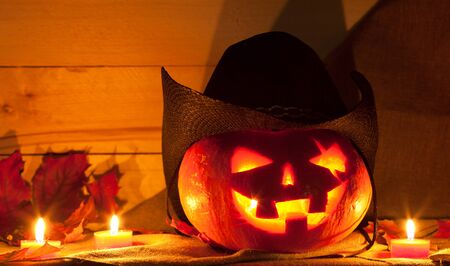 no teeth smile: Jack O Lantern in a cowboy hat on the table. Pumpkin carved for Halloween Stock Photo