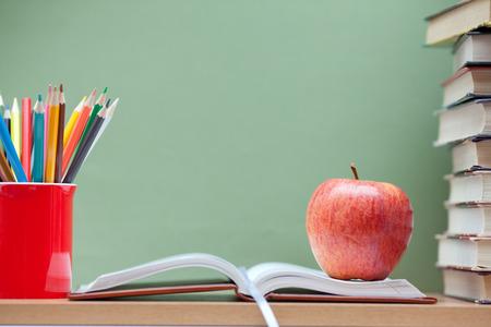 Buntstifte in einer Tasse, in den Büchern und in einem Apfel Standard-Bild