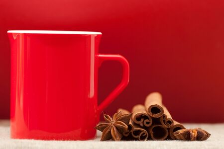 background red: Beautiful red cup on a red background and spices