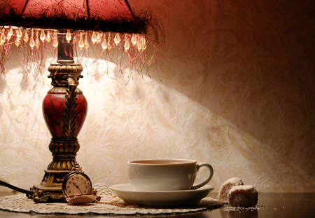 tea lamp: cup of tea, lamp and clock on the table Stock Photo