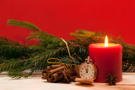 Red candle, pocket Watches, and Christmas tree on the red background
