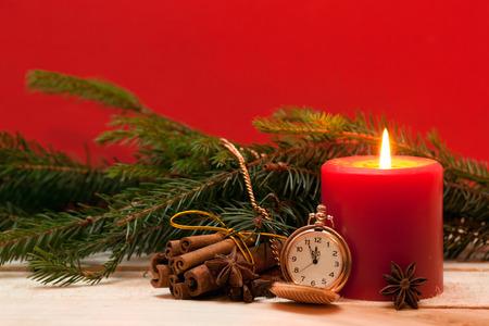 decoracion mesas: Vela roja, relojes de bolsillo, y el �rbol de Navidad en el fondo rojo