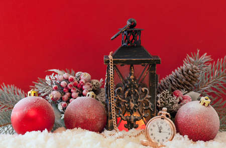 red lantern: Candle lantern, christmas balls and pocket watch in the snow with a red background