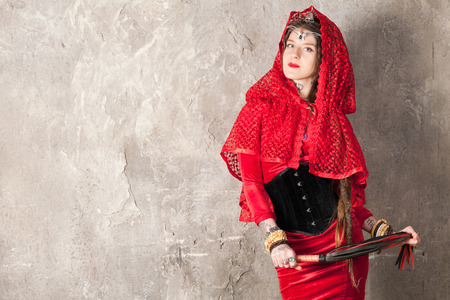 sadomasochism: Beautiful young woman with a whip near the wall Stock Photo
