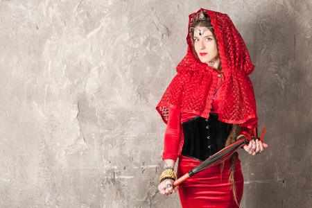 Schöne junge Frau mit einer Peitsche in der Nähe der Wand