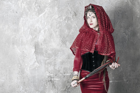 velvet dress: Beautiful young woman with a whip near the wall Stock Photo