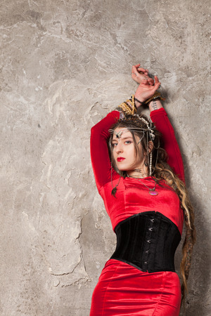 velvet dress: Beautiful woman in a dress and corset near the wall