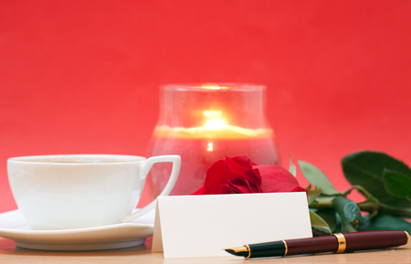 red sign: Red rose, candle, sheet of paper and cup of coffee on the table Stock Photo