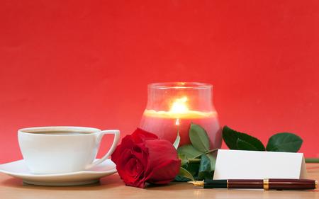 fondo rojo: rosa roja, velas, hoja de papel y una taza de caf� sobre la mesa