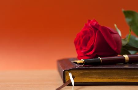 Notebook, vulpen en een roos op de tafel