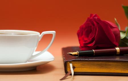Notebook, vulpen en een roos op de tafel Stockfoto