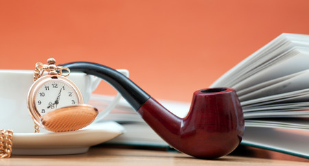 smoking pipe: Cup of coffee and a smoking pipe on the table Stock Photo