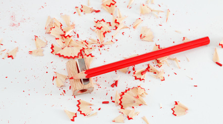 Red pencil and sharpener on white. Photos school supplies