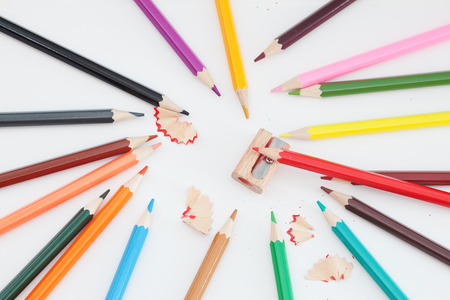 Colored pencils and sharpener on white. Photos school supplies Stock Photo