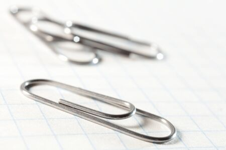 Iron clip closeup on notebook sheet closeup. Photos office appliances Stock Photo