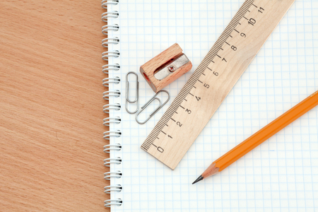 Ruler, pencil and sharpener lie on notebook. Photos office appliances