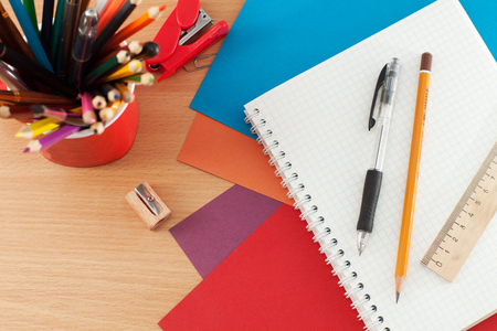 Colored pencils, notebook, ruler and pen on the table