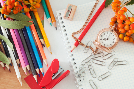 Colored pencils and a notebook on the table. Photos school supplies
